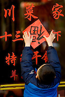 A little boy hangs up a sign with the Chinese character 'fu' meaning 'happiness' in Shanghai, China, on January 24, 2009. The character is placed on purpose upside down to make a play on words in Chinese between 'upside down' and 'arrived' which are homophenic. Therefore it can be read as 'happiness arrived'. Photo by Lucas Schifres/Pictobank