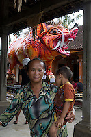woman with cild in Tegalalang in front of a Ogoh-Ogoh sculpture (demon spirit) shaped as awild pig in orange color, Central Bali. Balinese New Year called Nyepi (around march according to lunar calendar),  is a silent day of meditation and spiritual purification. One day before exorcist rituals are held for purification and balance of polar powers of the universe, first at noon by a priest (exorcism called Caru or Tawur Agung) and later on after sunset in a popular, carneval-like procession of Ogoh-Ogoh, symbolizing bhuta kali (demon, bad spirits,bad habits),  so all the bad spirits leave the village and the island.  Loud, rhythmic music and special performances are part of the procession called Ngerupuk. Road crossings are major spots of exorcism and special ogoh-ogoh performance, since demons often like to dwell here. At Nyepi, the following day, there is 24 hours silence, no vehicle or people on the street, no light or fire, no working - all the bad spirits should think, the island is abandoned and leave the island. Day after Nyepi is a day of reconciliation - new year starts purified.