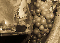 Red wine in glass and pinot noir grapes in a sepia tone with reflection of sun in glass create nice background