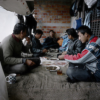 Refugees eat breakfast in the building where they are squatting before they head to the port to try to move on. Patras is home to about 3,000 illegal immigrants. Most of them are Afghans, although there are also some Iranians and Uzbeks. They stop in Patras to try and find passage to various European destinations by hiding in ships, containers and trucks parked in the port. If they are lucky they will make it to their destination. Many of them live in shacks made from cartons, plastic and wood they found on the beach. To shelter from the cold they also squat in abandoned buildings, living without water and electricity. The living conditions are inhumane and unhygienic.