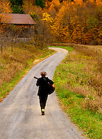 "Man walking on vermont country road playing guitar from behind, M. Jermyn ""The Minstrel"", Fall 2011"