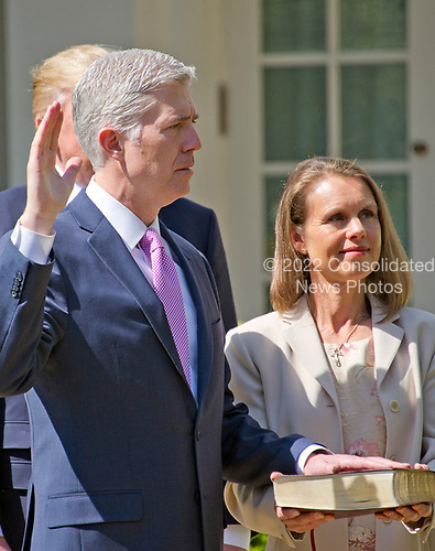 Associate Justice of the United States Supreme Court Neil Gorsuch takes the Oath of Office from Associate Justice Anthony Kennedy in the Rose Garden of the White House in Washington, DC on Monday, April 10, 2017.  Gorsuch's wife Louise holds the Bible.<br /> Credit: Ron Sachs / CNP<br /> (RESTRICTION: NO New York or New Jersey Newspapers or newspapers within a 75 mile radius of New York City)