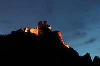 Padern Castle or Chateau de Padern, 12th century Cathar castle, Padern, Corbieres, Aude, France. This nighttime view shows the castle illuminated against the night sky. Picture by Manuel Cohen