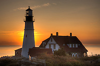 The sun rises behind the Portland Head Light, built in 1791, which protects mariners entering Casco Bay.  The lighthouse is located in Fort Williams Park, Cape Elizabeth, Maine.