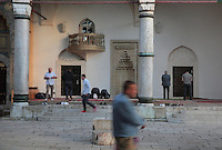 Men removing their shoes and praying in the courtyard of the Gazi Husrev-beg Mosque, built 1530-32, Sarajevo, Bosnia and Herzegovina. The complex includes a maktab and madrasa (Islamic primary and secondary schools), a bezistan (vaulted marketplace)and a hammam. The mosque was renovated after damage during the 1992 Siege of Sarajevo during the Yugoslav War. Picture by Manuel Cohen