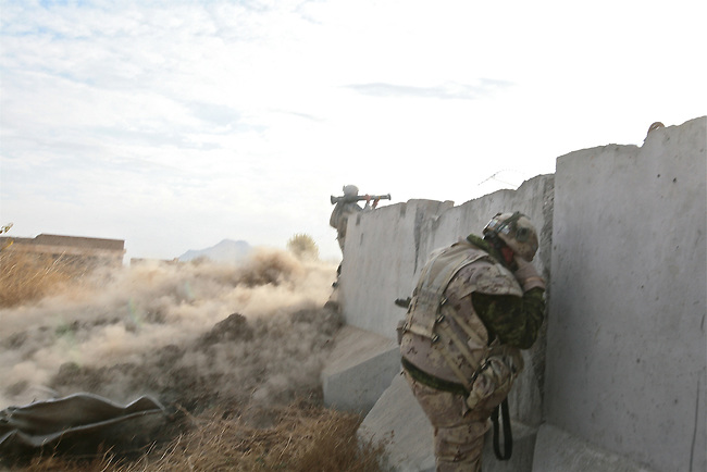 A Canadian soldier covers his ears as Staff Sgt. Aaron Kim, 28, of Scottsdale, Ariz., a soldier with Company B, 1st Battalion, 12th Infantry Regiment, fires an anti-tank rocket at a spot where Taliban fighters are believed to be hiding on a mountainside near the village of Ashoque, in Zhari district, Kandahar province, Afghanistan. Dec. 3, 2009. DREW BROWN/STARS AND STRIPES