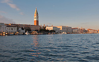 View across the lagoon to the St Mark's Campanile or Campanile di San Marco, the bell tower of the basilica, built 1541, St Mark's Basilica or Basilica San Marco, the Marciana Library or Biblioteca Marciana and the Doge's Palace or Palazzo Ducale, Venice, Italy. Many of the houses and palazzos fronting the canals and lagoon are in Venetian Gothic style, a style originating in the 14th century and combining Gothic lancet arches with Byzantine and Moorish influences. The city of Venice is an archipelago of 117 small islands separated by canals and linked by bridges, in the Venetian Lagoon. The historical centre of Venice is listed as a UNESCO World Heritage Site. Picture by Manuel Cohen