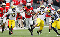 Ohio State Buckeyes quarterback Braxton Miller (5) rumbles upfield past Michigan defenders Michigan Wolverines cornerback J.T. Floyd (8), linebacker Jake Ryan (47) and defensive back Raymon Taylor (6) during the third quarter of the NCAA football game at Ohio Stadium in Columbus on Nov. 24, 2012. (Adam Cairns / The Columbus Dispatch)