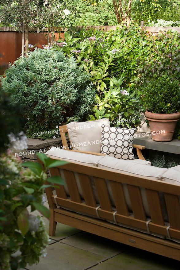 Mixed planting beds of perennials and shrubs border the seating area of this Seattle backyard.