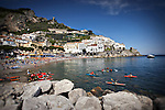 Landscape photo of the view of the Amalfi Coast in Italy with people kayaking in the water.