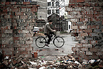 A man bicycles past a construction site in Yangzhou, China, a suburb city of Shanghai and major producer of photovoltaic cells for solar power.