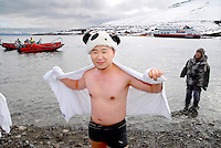 photograph by XAVIER CERVERA 06/2010.A funny chinese adult after swimming at 1.7 ° C water temperature on the stony beach of Skansbukta, in Billefjorden (close to Longyearbyen capital) in Spitsbergen island, Svalbard archipielago, Norway. Behind them, 'zodiac' for landing, and norwegian vessel MS Fram