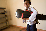 Bunroeun goes home. He is taught classical violin at the Phnom Penh school of 'Beaux Arts' outside Phnom Penh..A Khmer boy learns to play classical violin at the school of Beaux Arts, at the edge of Cambodia's capital, Phnom Penh. He is an orphan and comes from a poor family. His parents died long ago, from AIDS related diseases. He lives with his grandmother and his uncle, and their family. He lives on the top floor of an apartment block, where his family run a textile business, sewing together clothes and ornamental flags from around the world. A dozen young women work in this textile business, and the boy's home space is actually amidst this small factory environment which he shares with them. They eat, work and play together like an extended family or community. Phnom Penh, Cambodia