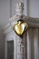 Detail of a gold glass decoration in the shape of a heart hanging from a piece of furniture