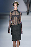 Model walks runway in a charcoal cable lace long sleeve top with melton epaulette and high neck collar over charcoal melton strapless bra, with charcoal melton pencil skirt with cut-out detail, from the Vera Wang Fall 2012 Vis-a-gris collection, during Mercedes-Benz Fashion Week Fall 2012 in New York.