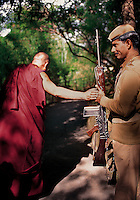 The Dalai Lama blessing his guard holding a rifle   <br /> Dharamsala, India 1998<br /> I first met His Holiness the Dalai Lama in 1988 and have had the great fortune to photograph him a number of times over the years. I&rsquo;ve always enjoyed our conversations but sometimes it&rsquo;s his gestures that hold the most meaning. One day we were walking through the lovely bamboo shaded lane from his home to his office as we passed one of his ever-present guards. Suddenly the Dalai Lama stopped. Placing one hand on the soldier&rsquo;s hand holding the rifle, he chanted a prayer and moved on. I quickly lifted my camera and managed to take one frame. The guard simply beamed.