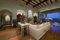 Mediterranean decore family room with white couches and elaborately wood beamed high ceiling, and pocket doors that open to the outside