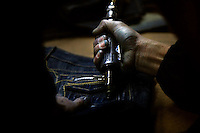 A textile worker drills holes in a pair of jeans at a garment factory. The factory, which specifically carries out a wear-and-tear process used to achieve a fashionable distressed look, produces approximately 10,000 pairs of jeans every day. Thousands of workers labour through the night scrubbing, spraying and tearing jeans in order to meet the production demand. The factory is owned by Huang Dehong, who left his impoverished village and arrived penniless in Zhongshan twenty years ago. China, the &quot;factory of the world&quot;, is now one of the world's largest producers of jeans and its textile workers are among the 200 million migrant labourers criss-crossing the country looking for a better life.