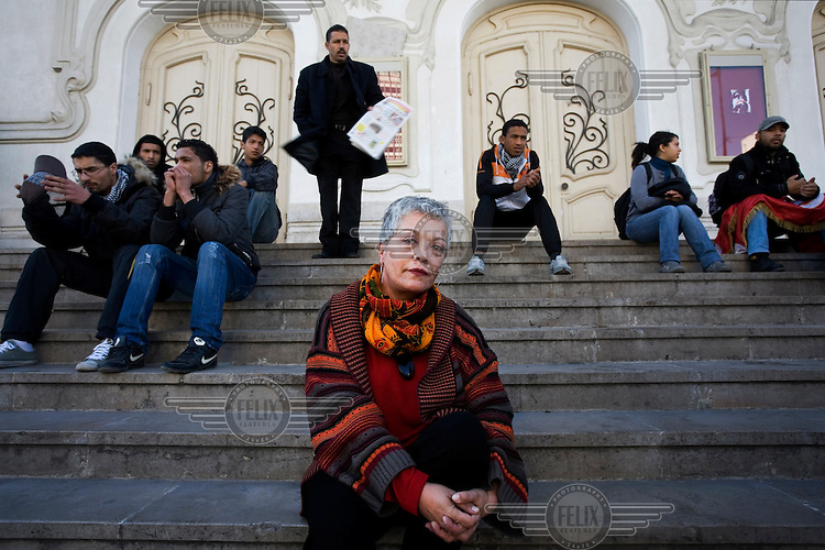 Frida Dahmani, journalist for Jeune Afrique magazine sits on the steps in front of the National Theatre..