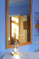 Next to an antique gilt-framed mirror in the dining room open glass shelving displays blue and gold glasses