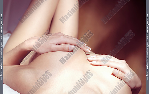 Nude woman lying in bed with hands covering her breasts