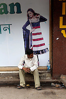 A man sits next to an advertisement in a market in central Kolkata.<br /> <br /> To license this image, please contact the National Geographic Creative Collection:<br /> <br /> Image ID: 1925731 <br />  <br /> Email: natgeocreative@ngs.org<br /> <br /> Telephone: 202 857 7537 / Toll Free 800 434 2244<br /> <br /> National Geographic Creative<br /> 1145 17th St NW, Washington DC 20036