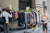 Customers browse racks of discounted merchandise at a sample sale in New York on Thursday, October 2, 2014. (© Richard B. Levine)