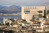 Italy. Lombardy region. Campione d'Italia. Campione d'Italia is occupying an enclave within the Swiss canton of Ticino, separated from the rest of Italy by Lake Lugano and mountains. Campione d'Italia takes advantage of its status by operating a famous casino, the Casinò di Campione, as gambling laws are less strict than in both Italy and Switzerland. The new Casinò di Campione was opened in 2007. It is the largest gambling place in Europe and replaces the existing 1936 casino. The project  was designed by famed Swiss architect Mario Botta. The external finish in gilded stone slabs arranged in alternating bush-hammered and smooth bands acts as a link between the modern 21th-century buildings of Campione d'Italia and the old town center. The complex consists of three large buildings, the main central block rising to ten storeys on the piazzale side. On the other side of the lake, the town of Lugano. 1.03.2008 © 2008 Didier Ruef