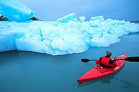 Kayaker paddles around a floating iceberg in Nellie Juan Lagoon in Prince William Sound, Alaska.