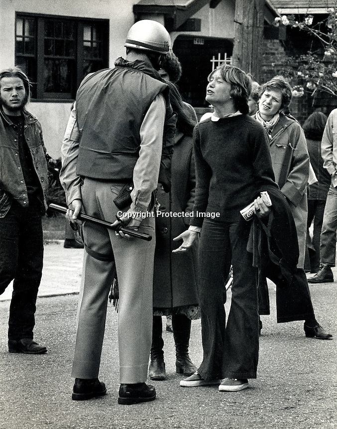 Demonstration on Rosevelt St. in Berkeley, Ca 1970..Berkeley Policeman and unidentified girl. .(photo by Ron Riesterer)