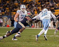 Pitt defensive lineman Shakir Soto (52) attempts to bring down North Carolina quarterback Marquise Williams but is flagged for grabbing the facemask. The North Carolina Tar Heels football team defeated the Pitt Panthers 26-19 on Thursday, October 29, 2015 at Heinz Field, Pittsburgh, Pennsylvania.
