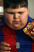 Dzhambulat Khotokhov, 6, one of the fattest boys in the world, eats a burger in Nal'chik, near his hometown Terek in southern Russia. .Now 1.4 metres tall and weighing about 100 kg, Khotokhov has grabbed world attention as the biggest kid in the world since he was three. .Khotokhov lives with his mother Neyla and his brother, 14-year-old Mukha. .
