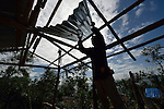 Rene de la Cruz puts a roof on his new house three months after he lost his old one to Typhoon Haiyan, which ravaged a wide swath of the Philippines in November 2013. He lives on Manipulon, a small island off the coast from the town of Estancia. The storm was known locally as Yolanda. Residents of this island have received some assistance from the ACT Alliance.