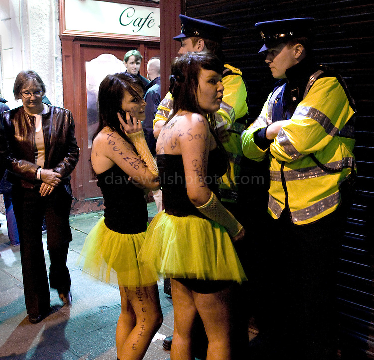 Two girls in dayglo skirts talking to Gardai in Dublin's Temple Bar, St. Patrick's Day, 2009