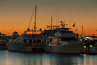 The pre-sunrise sky glows orange behind pleasure boats docked in one of the inner harbor marinas in Baltimore, Maryland.