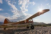 Bush pilot Dirk Nickisch of Coyote Air, on a landing strip in his De Havilland Beaver, along the Canning River, Arctic National Wildlife Refuge, Brooks range mountains, Alaska.