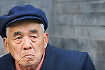 An elderly man sits by the side of a building in the Shichahai area and looks out at the Houhai Lake in Beijing,China.
