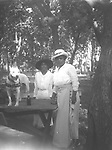PAMPERED PIT BULL. Two of the picnicking women seen in image LB019 show off their hats and the pit bull terrier. The breed may have been popular in Lincoln<br /> <br /> Photographs taken on black and white glass negatives by African American photographer(s) John Johnson and Earl McWilliams from 1910 to 1925 in Lincoln, Nebraska. Douglas Keister has 280 5x7 glass negatives taken by these photographers. Larger scans available on request.