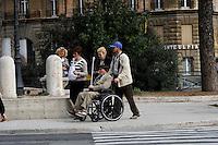 Anziano sulla sedia a rotelle in via dei Fori Imperiali aiutato da alcune persone.Elder wheelchair in via dei Fori Imperiali helped by some people
