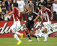 Jordan Graye #16 of D.C. United slides a pass between Mariano Trujillo #8 and Jesus Padilla #10 of Chivas USA during an MLS match at RFK Stadium, on May 29 2010 in Washington DC. United won 3-2.