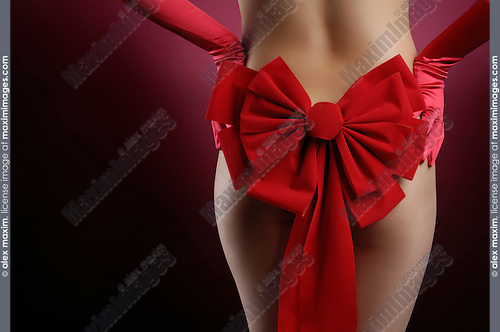 Sexy woman in red gloves with Christmas bow on her back