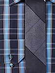 Closeup of a mens blue tartan collared shirt with a slim tie