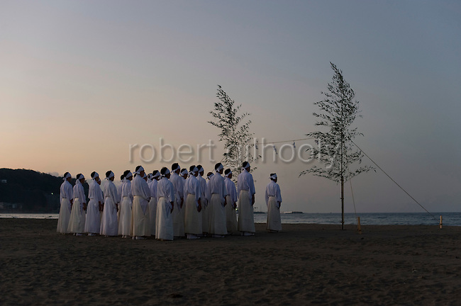 Shrine priests and officials look toward the sea during a purification ritual known as hamaorisai at the start of the 3-day Reitaisai festival in Kamakura, Japan on  14 Sept. 2012.  Photographer: Robert Gilhooly