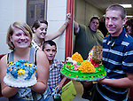 Photo by Phil Grout...Lineboro has one family where cake baking and decorating is a grand champion art form..The bidding for John Krebs' grand champion decorated cake has just brought in $475.at the Carroll County 4-H Fair cake auction.  On his way out of the auction hall,  John passes.his older sister, Jenna with the top tier of her grand champion tiered cake.  Several minutes later,.Jenna's cake netted $600.  ..