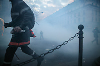 25 March 2004 - Paris, FRA - Firefighters are surrounded by tear-gas on the Place de l'Opera in Paris, 25 March 2004, as they confront riot police. The firefighters earlier marched through the city to demand that their profession be classified as a dangerous occupation which entails various social security benefits including early retirement. The violence left 2 firefighters and 20 policemen injured.