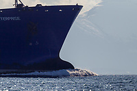 The watchman stands on the bow of the Polar Enterprise oil tanker as it travels north into the Valdez arm, Chugach mountains range borders the channel, Prince William Sound, Alaska.