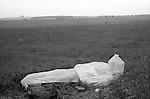 Free festival Stonehenge. Summer solstice 1976. Summer rain, hippy sleeps in a make shift  waterproof sleeping bag...