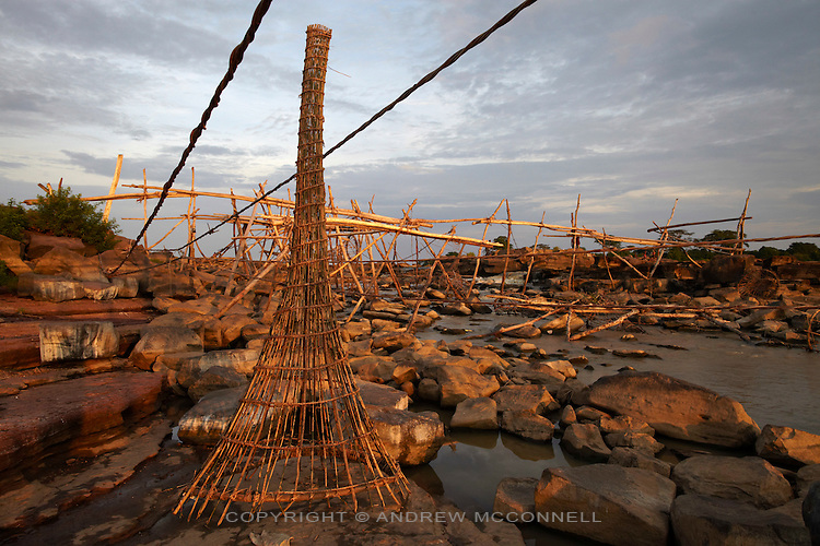 A basket is removed from the river as the water levels becomes too low to fish, at Wagenia Falls, DR  Congo. During the dry season the water levels drops to almost nothing and the fishing is poor, fishermen use this time to build new wooden frames before the rains begin and the rapids rise again.