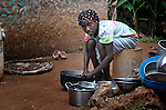 """Mislanda Ridore, 13, here washing dishes at her home, is a Peace Pal in the southern Haitian village of Mizak. Peace Pals is a program of the World Peace Prayer Society, which promotes the message """"May Peace Prevail on Earth"""" as a simple, universal expression to unite the hearts of all people in a common desire and hope for peace on Earth. Peace Pals provides a safe and nurturing environment for children to gather to play and learn lessons that organizers hope will lead to generational changes in attitudes about self-worth, care for the environment, personal health & hygiene, conflict resolution, respect for all persons and encouragement to be """"peacebuilders"""" at all levels. In Mizak, Peace Pals is sponsored by Haitian Artisans for Peace International (HAPI)."""
