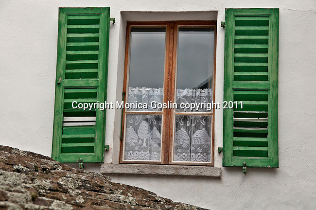 Window with green shudders and hand made lace curtains in Bondo, a Swiss Bregaglia Valley town in the Graubunden canton